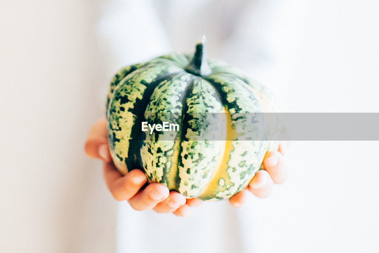 Cropped Hands Of Woman Holding Pumpkin