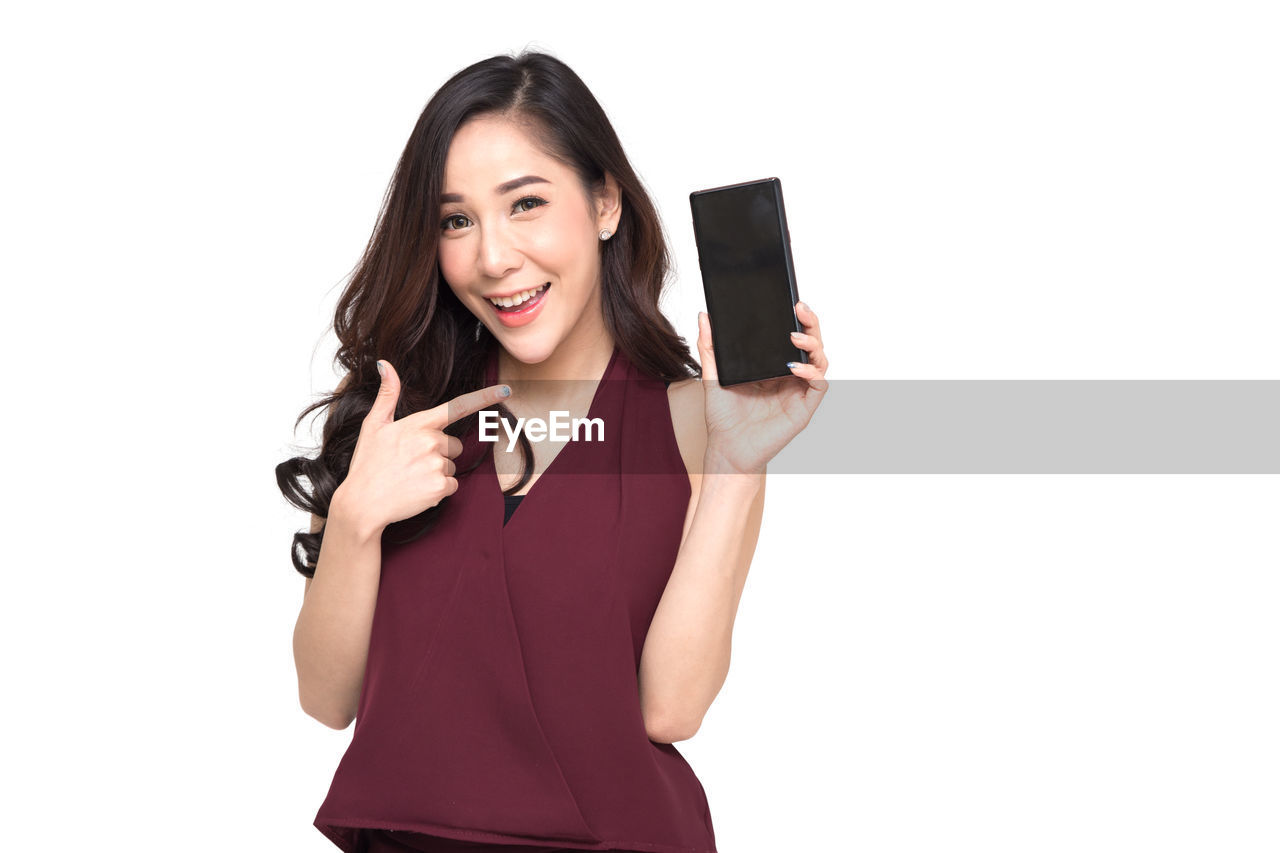 Young Woman Showing Phone While Standing Against White Background