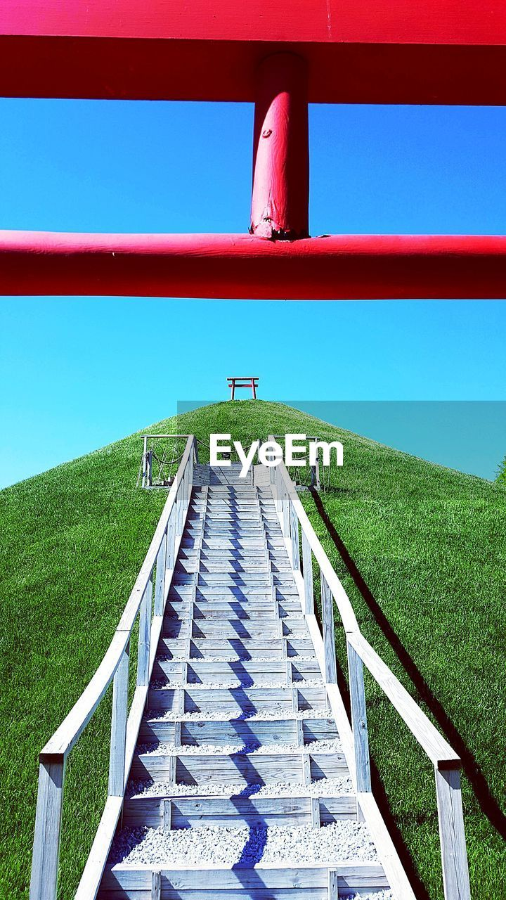Staircase on hill against clear blue sky
