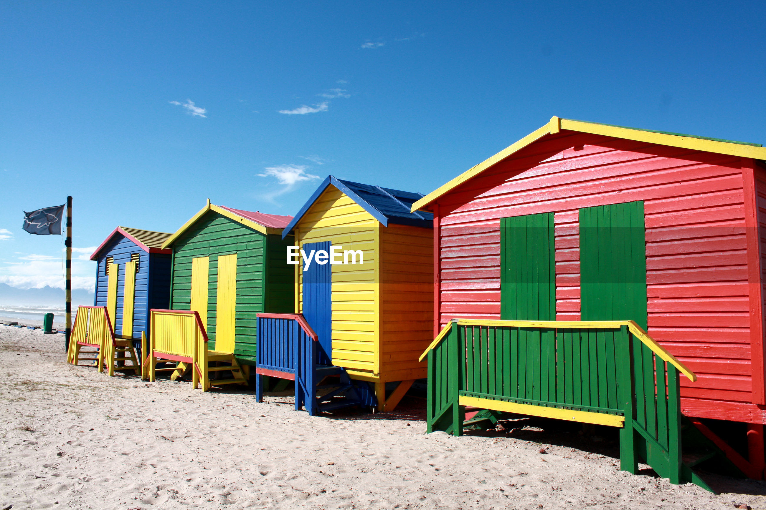 Colorful huts at sandy beach against sky