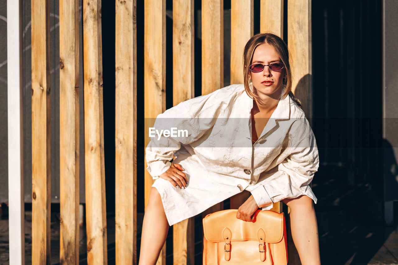 Portrait of young woman sitting against planks