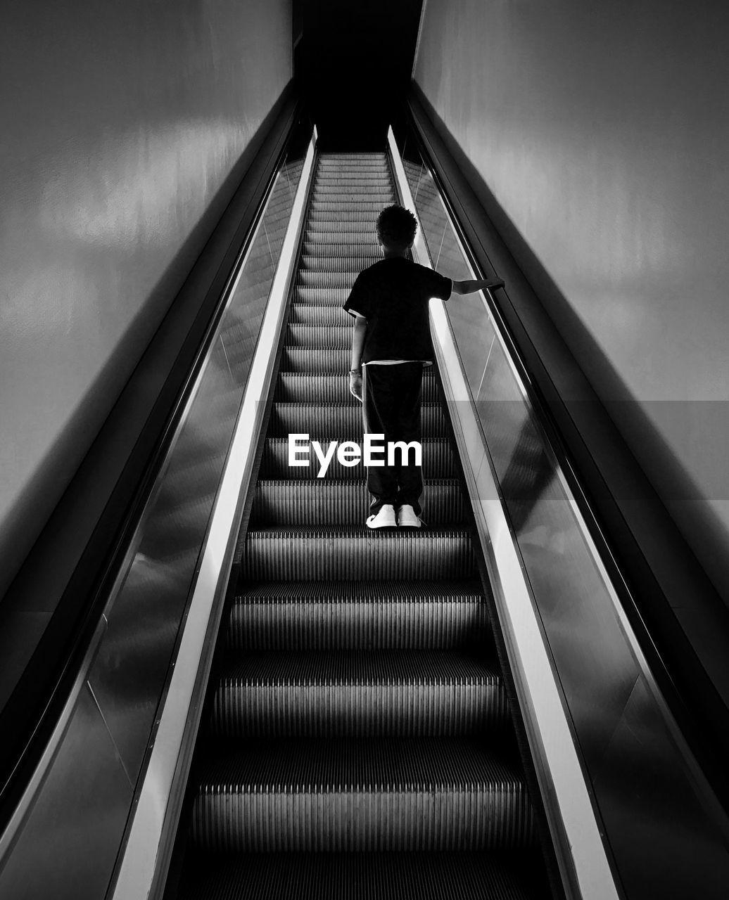 Rear View Of Boy Standing On Escalator