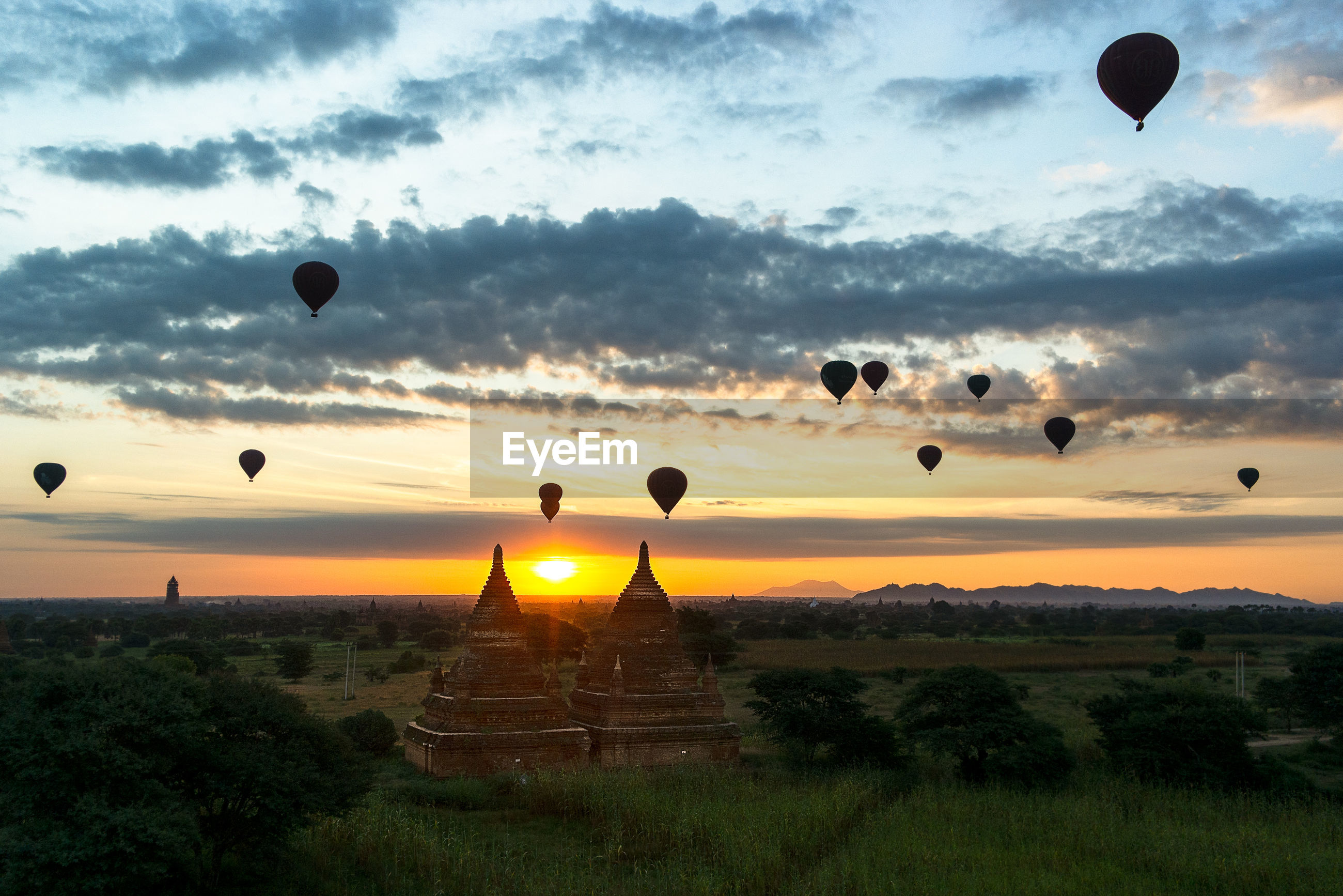 Hot air balloons flying over temples against sky during sunrise
