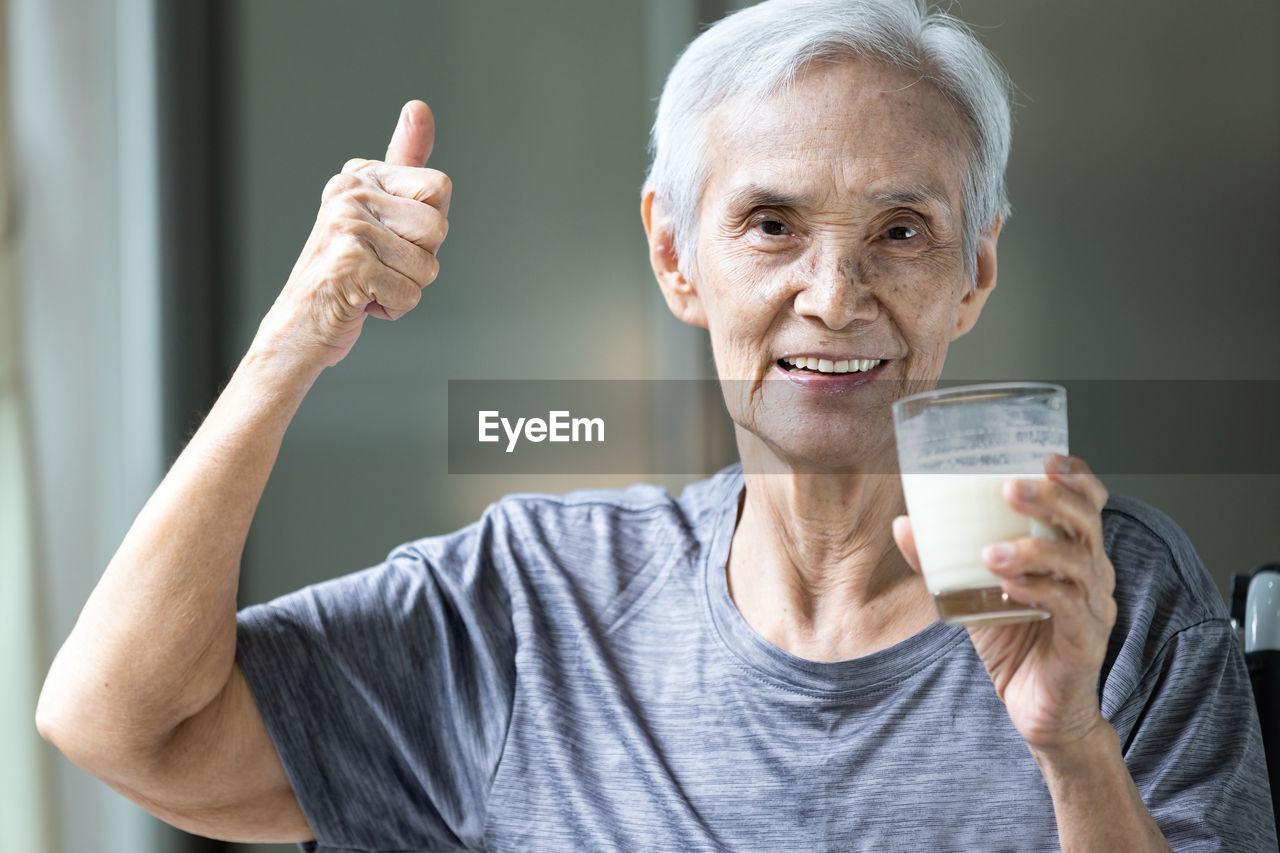 Portrait of senior woman gesturing while drinking milk