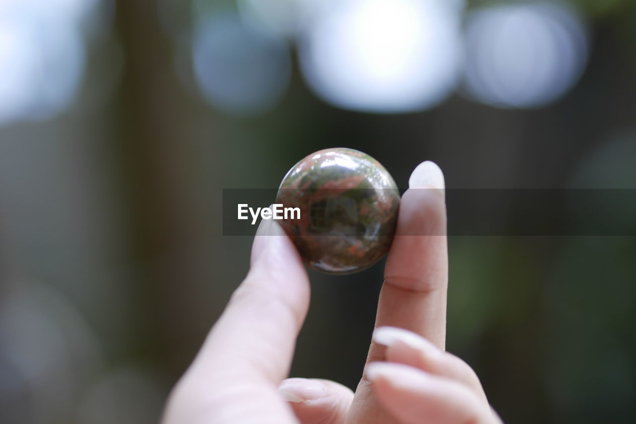 human hand, hand, holding, one person, human body part, real people, focus on foreground, day, sphere, close-up, finger, human finger, outdoors, body part, unrecognizable person, crystal ball, ball, leisure activity, nature