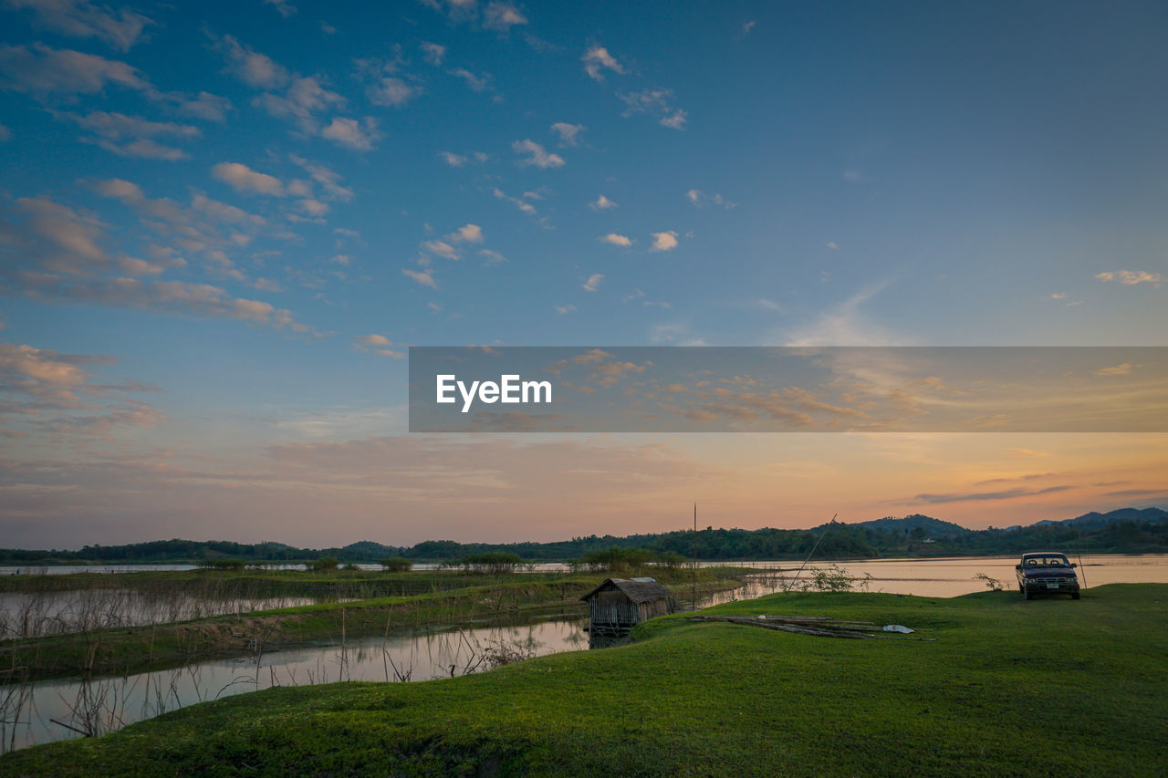 sky, scenics - nature, cloud - sky, sunset, beauty in nature, water, tranquility, grass, plant, tranquil scene, environment, field, land, landscape, nature, no people, green color, non-urban scene, outdoors