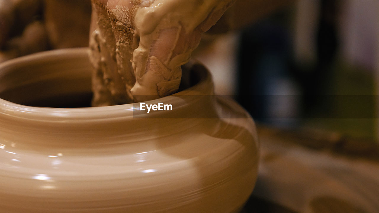 Cropped Hands Of Potter Making Pot On Pottery Wheel