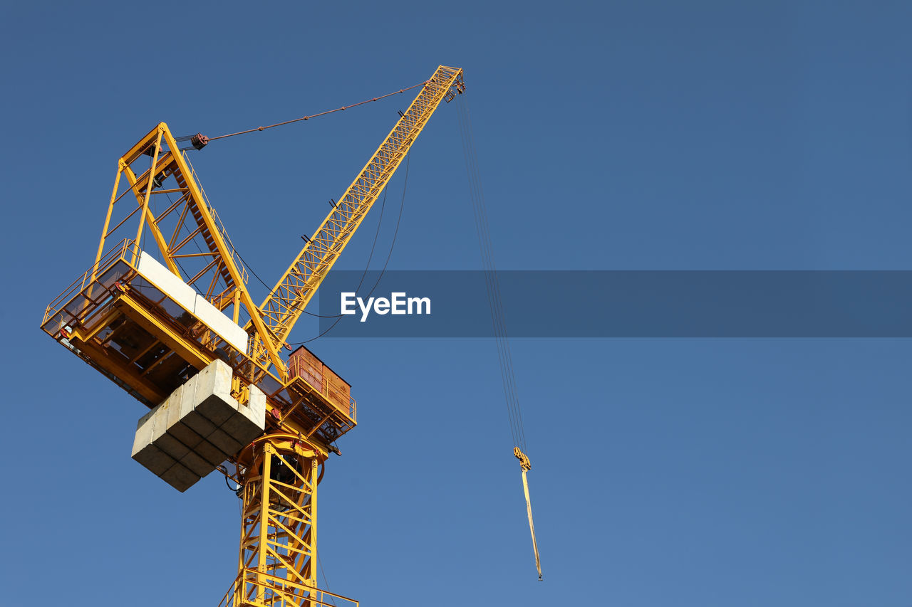 machinery, crane - construction machinery, construction industry, sky, construction site, development, industry, clear sky, tall - high, low angle view, nature, blue, no people, metal, day, architecture, built structure, construction machinery, copy space, outdoors, construction equipment, industrial equipment