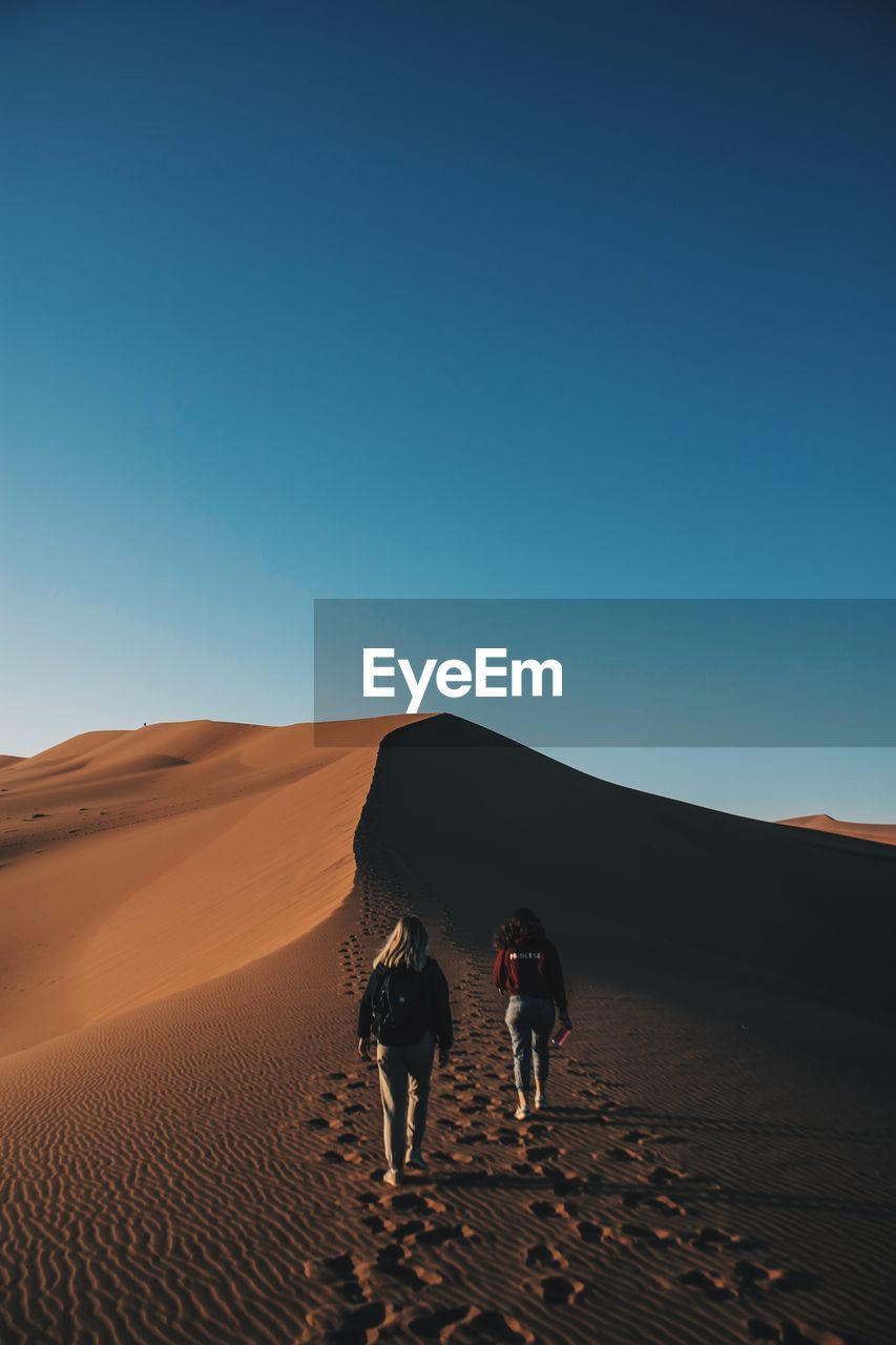 Rear View Of Friends Walking On Desert Against Clear Blue Sky