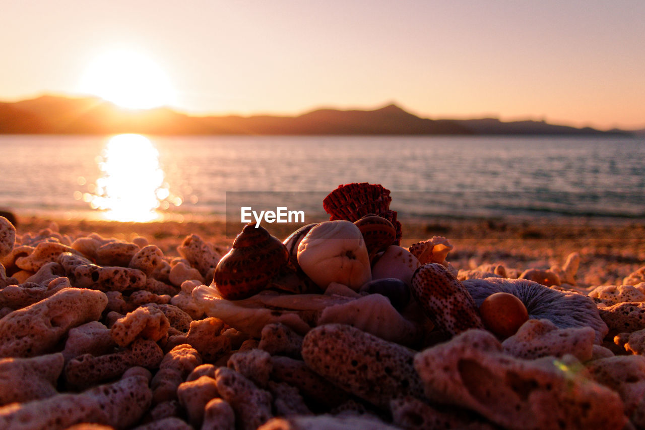 sunset, beach, sea, pebble, shore, nature, water, beauty in nature, sky, rock - object, no people, sand, outdoors, tranquility, scenics, pebble beach, horizon over water, tranquil scene, sunlight, clear sky, close-up, day