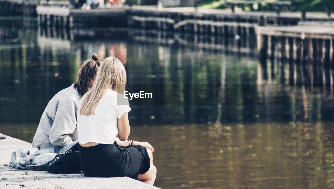 Women sitting at lakeshore