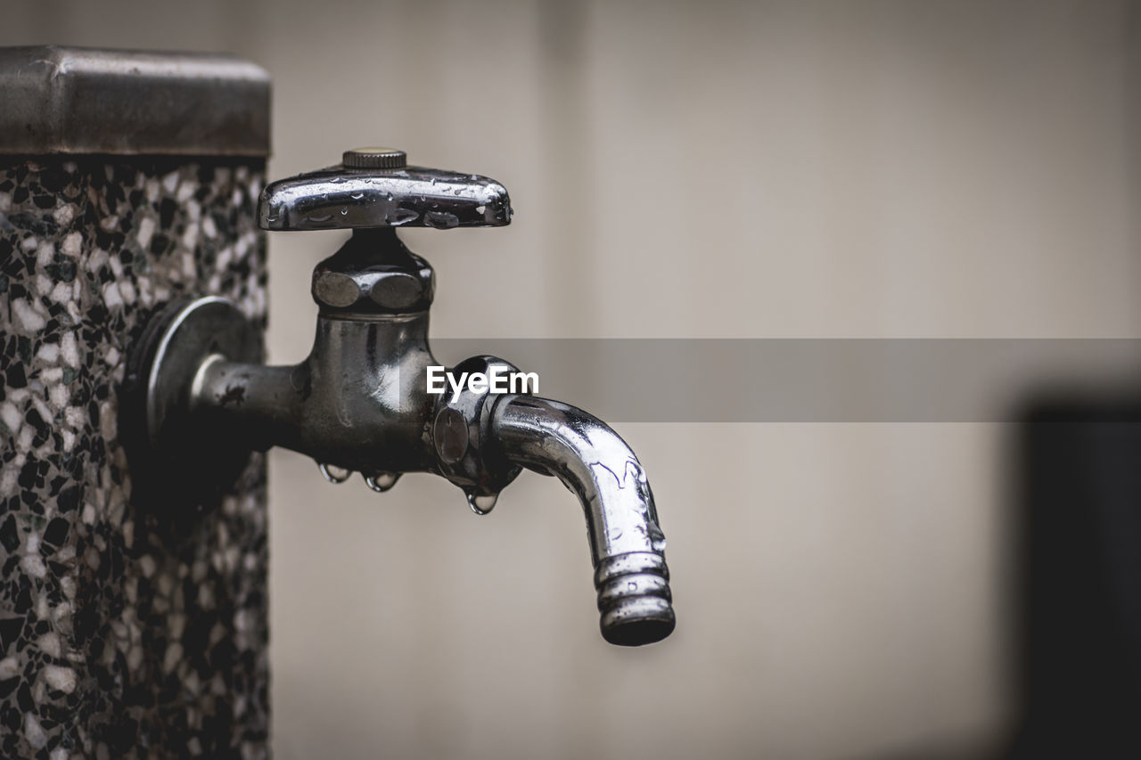 Close-Up Of Wet Metallic Faucet Attached On Wall