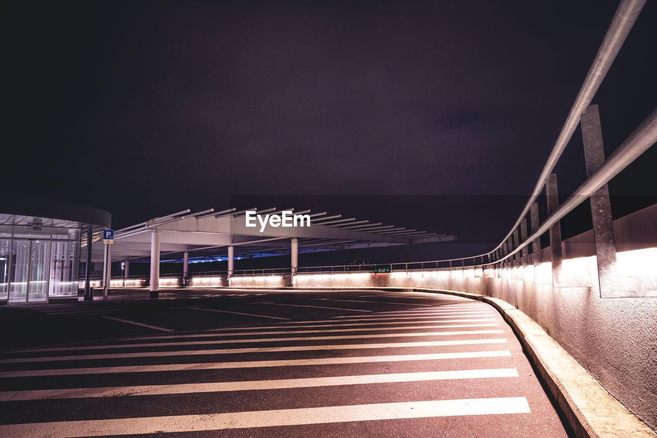 architecture, built structure, transportation, illuminated, night, bridge, bridge - man made structure, sky, connection, road, city, no people, nature, road marking, sign, building exterior, symbol, direction, marking, the way forward, outdoors, long