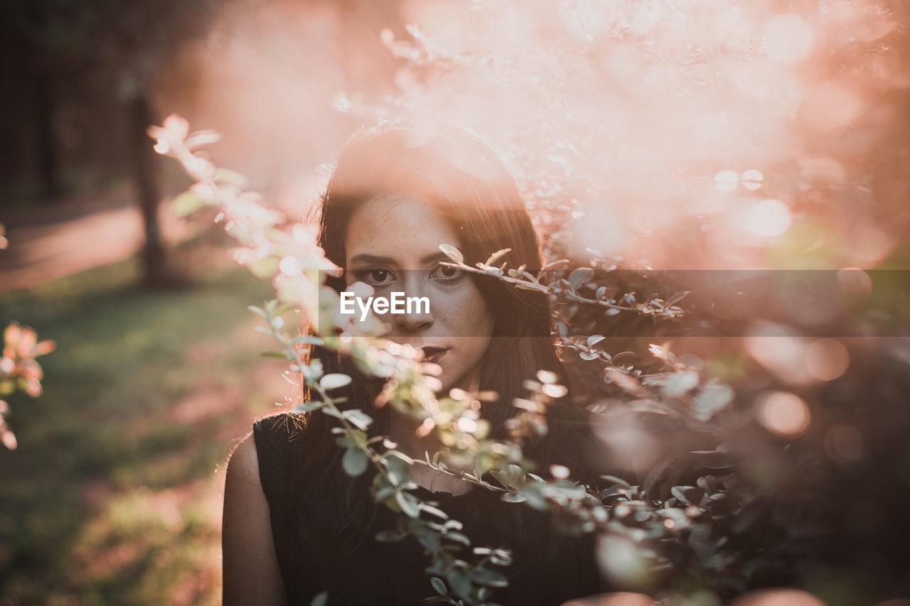 Close-up portrait of woman by plants