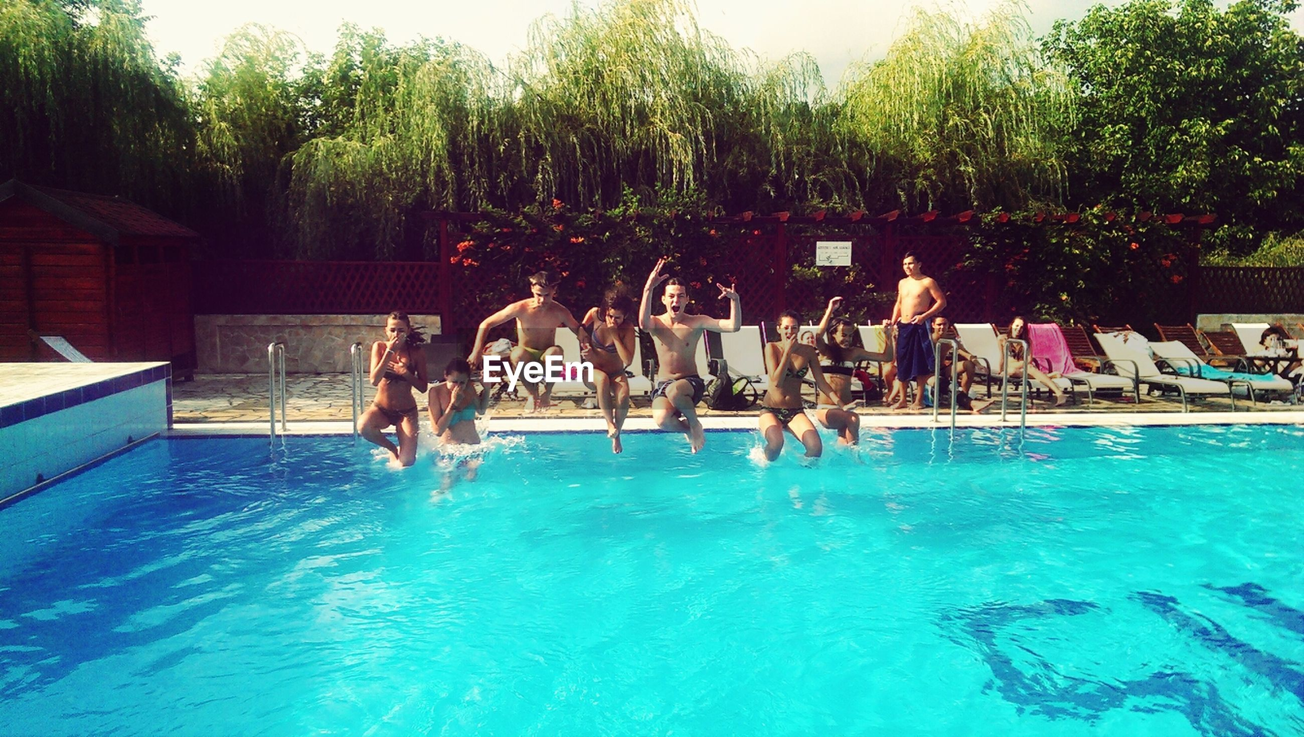 water, swimming pool, tree, lifestyles, leisure activity, vacations, enjoyment, waterfront, blue, large group of people, turquoise colored, sea, men, person, summer, fun, nature, tourist resort, built structure