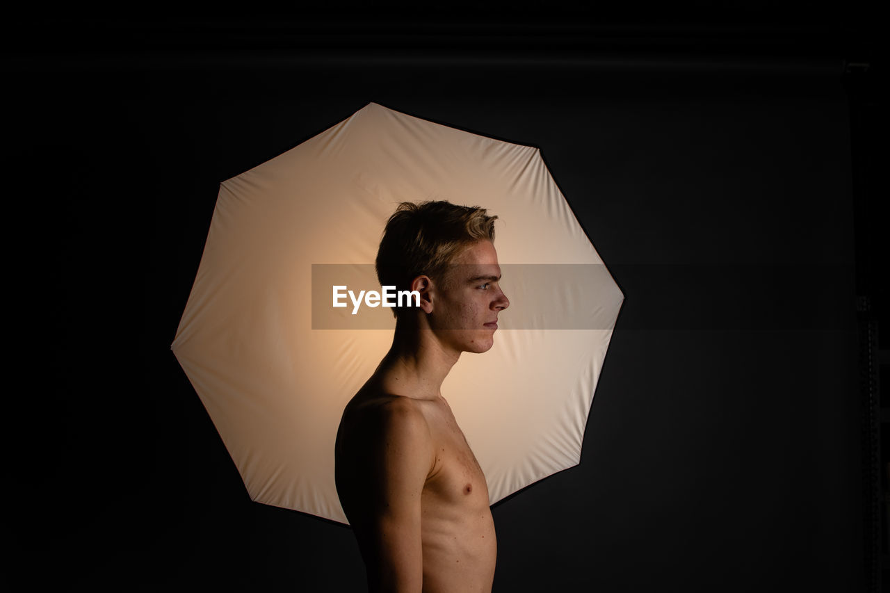 Shirtless young man with umbrella standing against black background