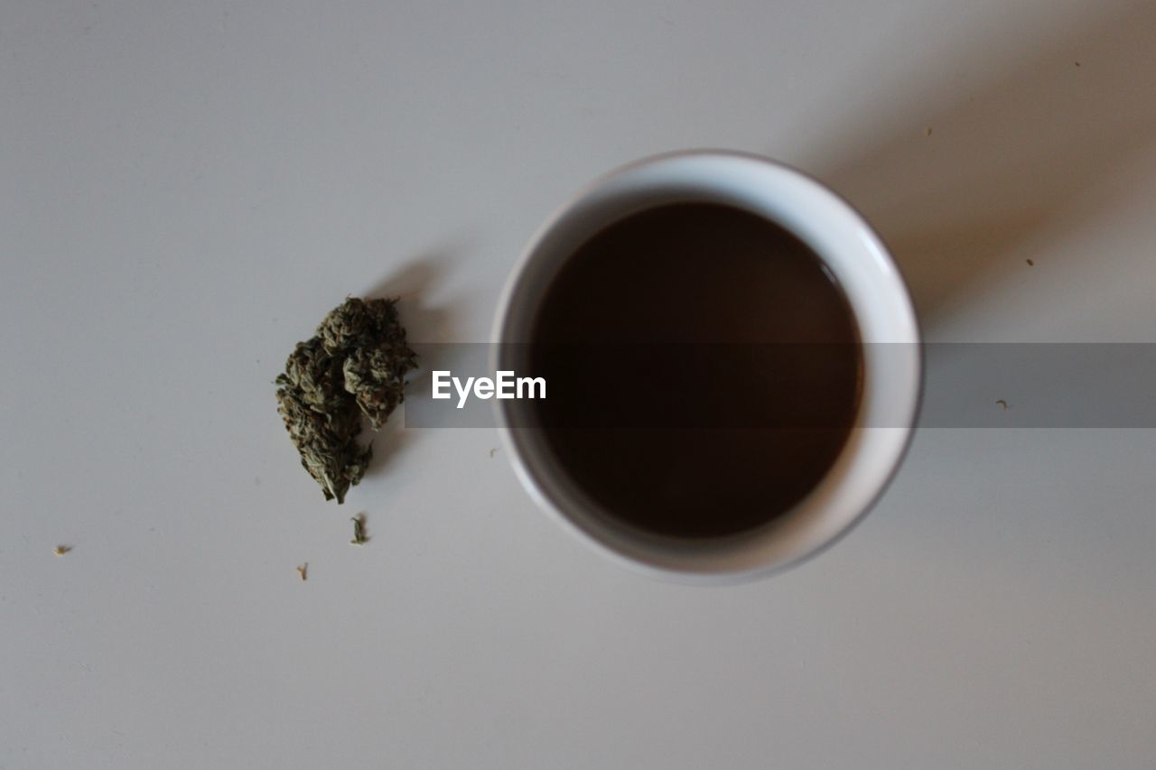 Directly above shot of tea cup with marijuana on white background