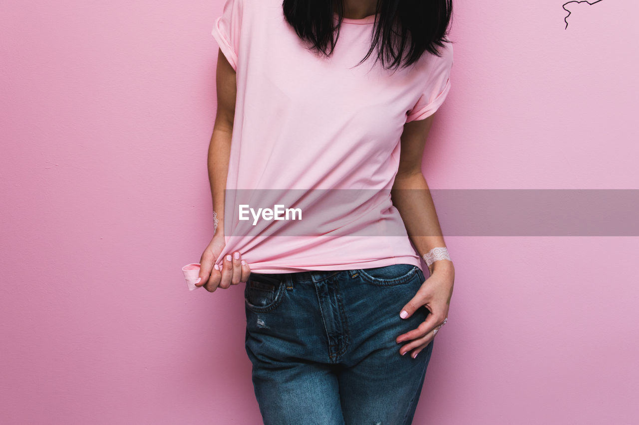 Midsection of woman standing against pink wall