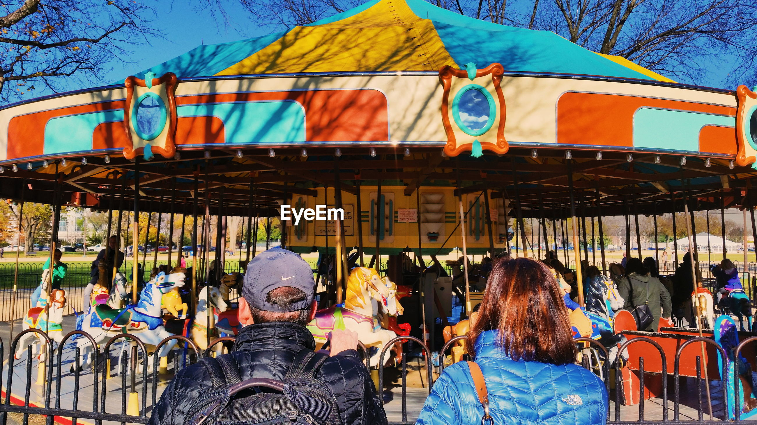 REAR VIEW OF PEOPLE ON AMUSEMENT PARK RIDE
