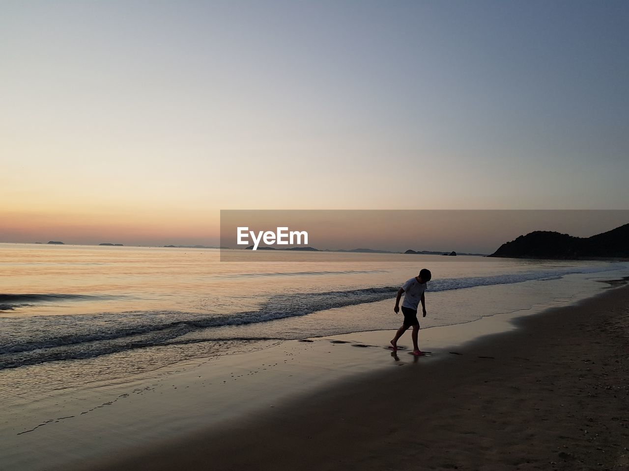 beach, sky, land, sea, water, real people, beauty in nature, sunset, full length, sand, scenics - nature, one person, men, walking, lifestyles, leisure activity, nature, clear sky, copy space