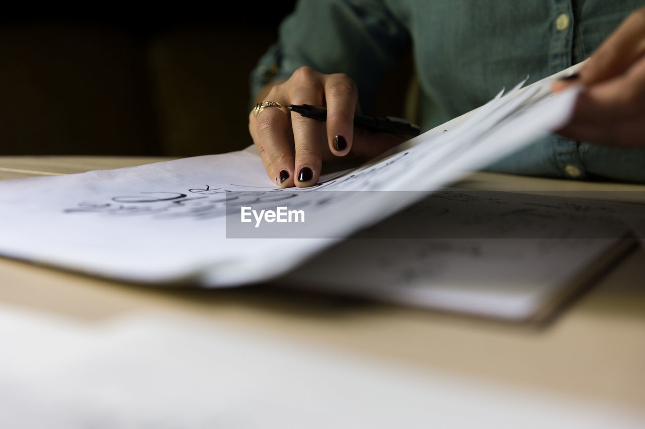 Cropped Image Of Woman Writing In Book At Table