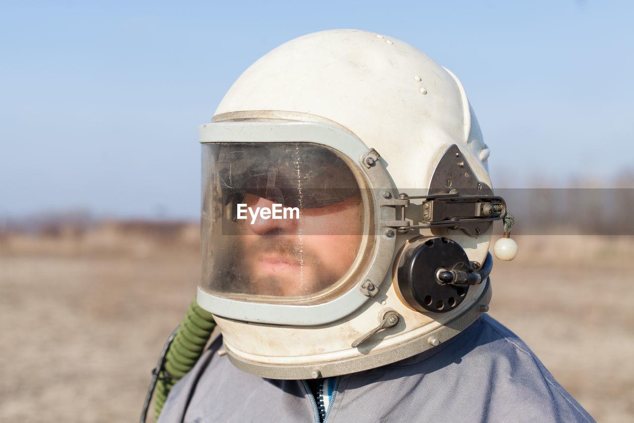 Close-Up Of Man Wearing Helmet On Field Against Sky