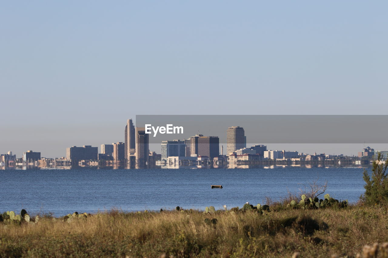 CITYSCAPE BY SEA AGAINST CLEAR SKY