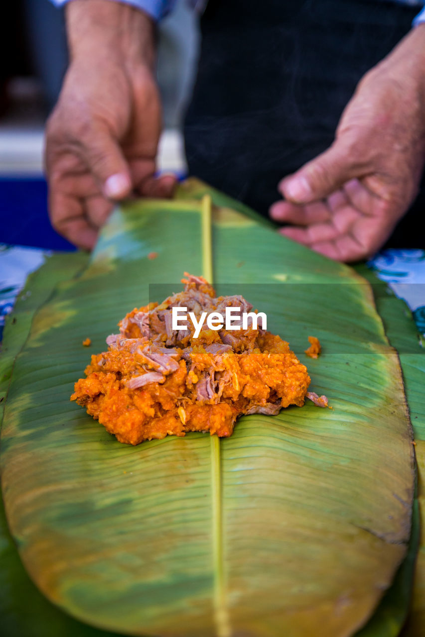 Midsection of man wrapping food in leaf