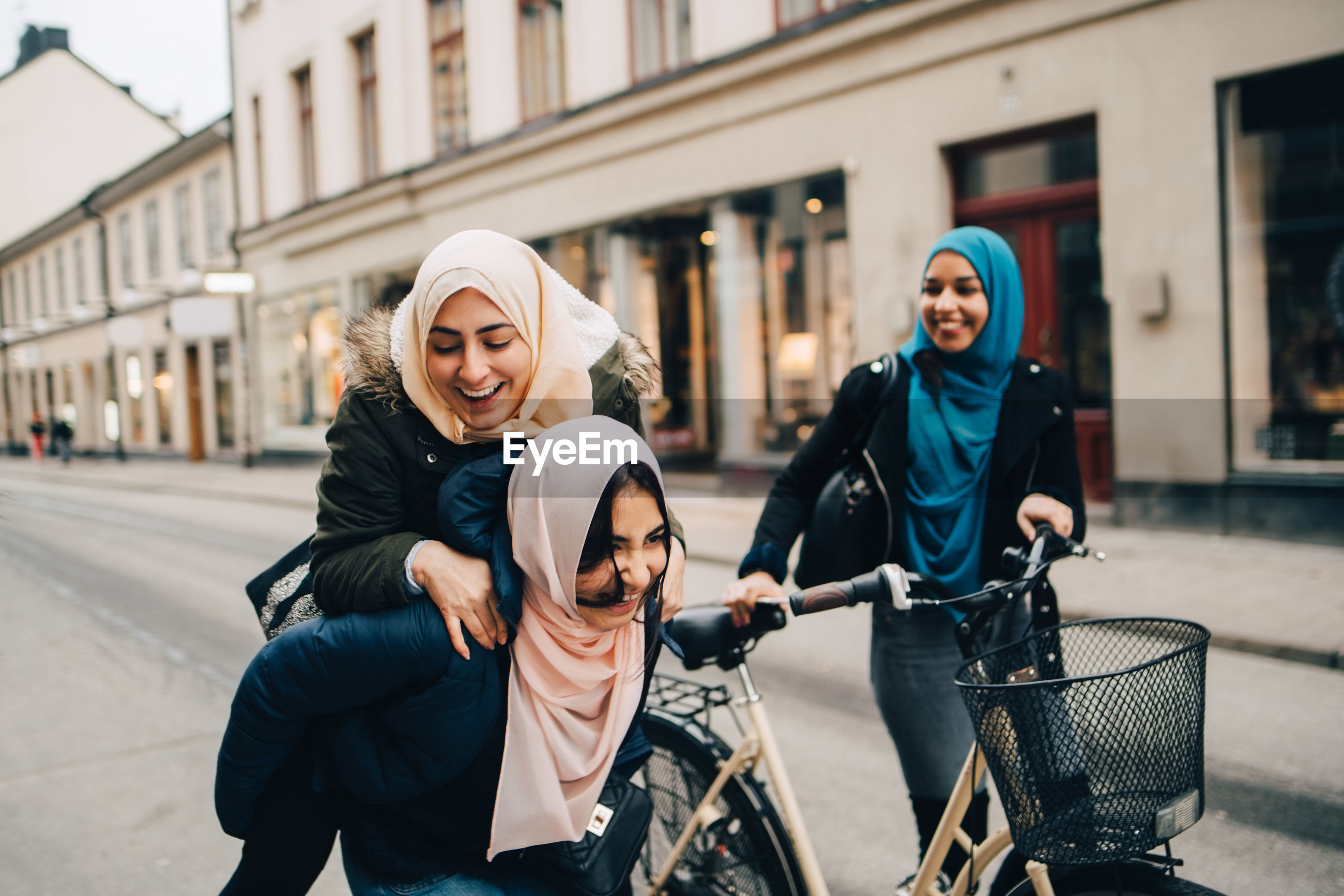 Cheerful teenage girl giving young woman piggyback by friend walking with bicycle on street in city