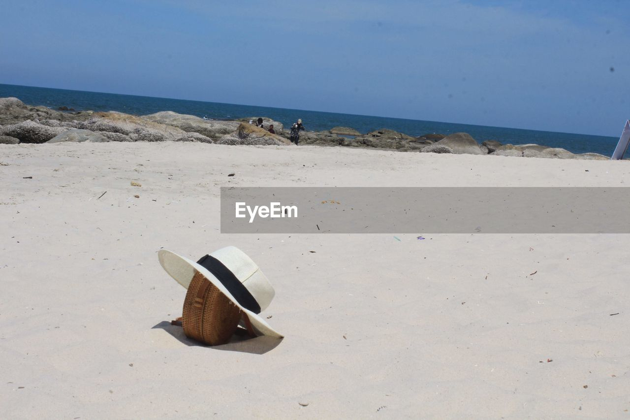 Hat and purse on sand at beach against blue sky