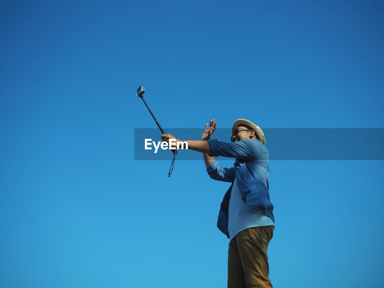 Low angle view of happy man taking selfie with monopod against clear blue sky