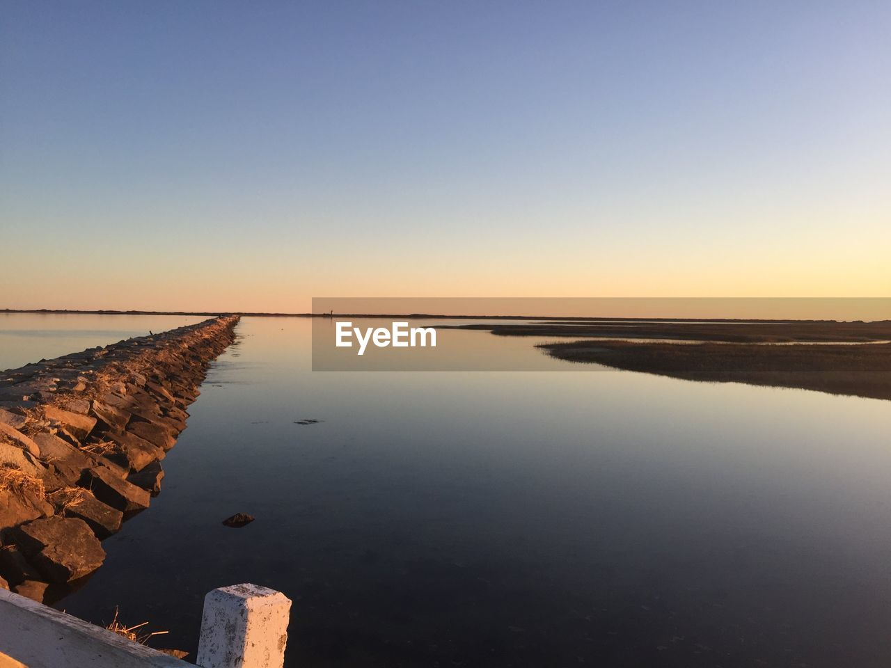 water, sky, scenics - nature, tranquility, copy space, reflection, tranquil scene, beauty in nature, sunset, clear sky, sea, nature, no people, non-urban scene, outdoors, idyllic, beach, standing water, groyne