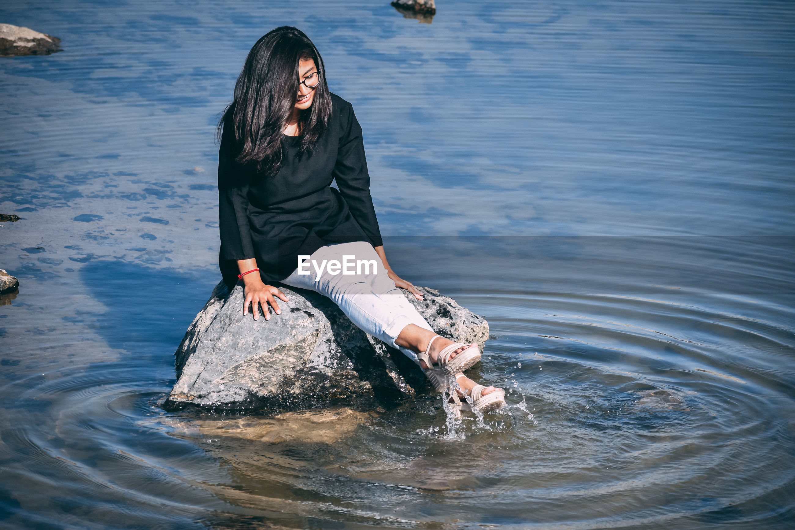 Young woman splashing water while sitting on rock in sea