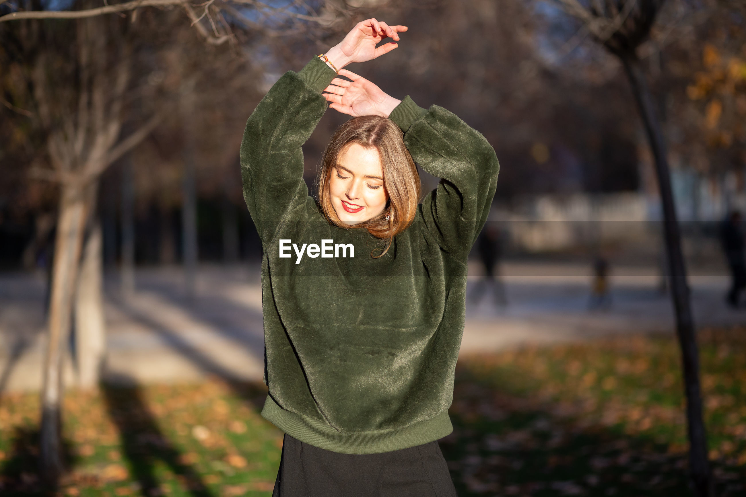 Smiling young woman standing at park during winter