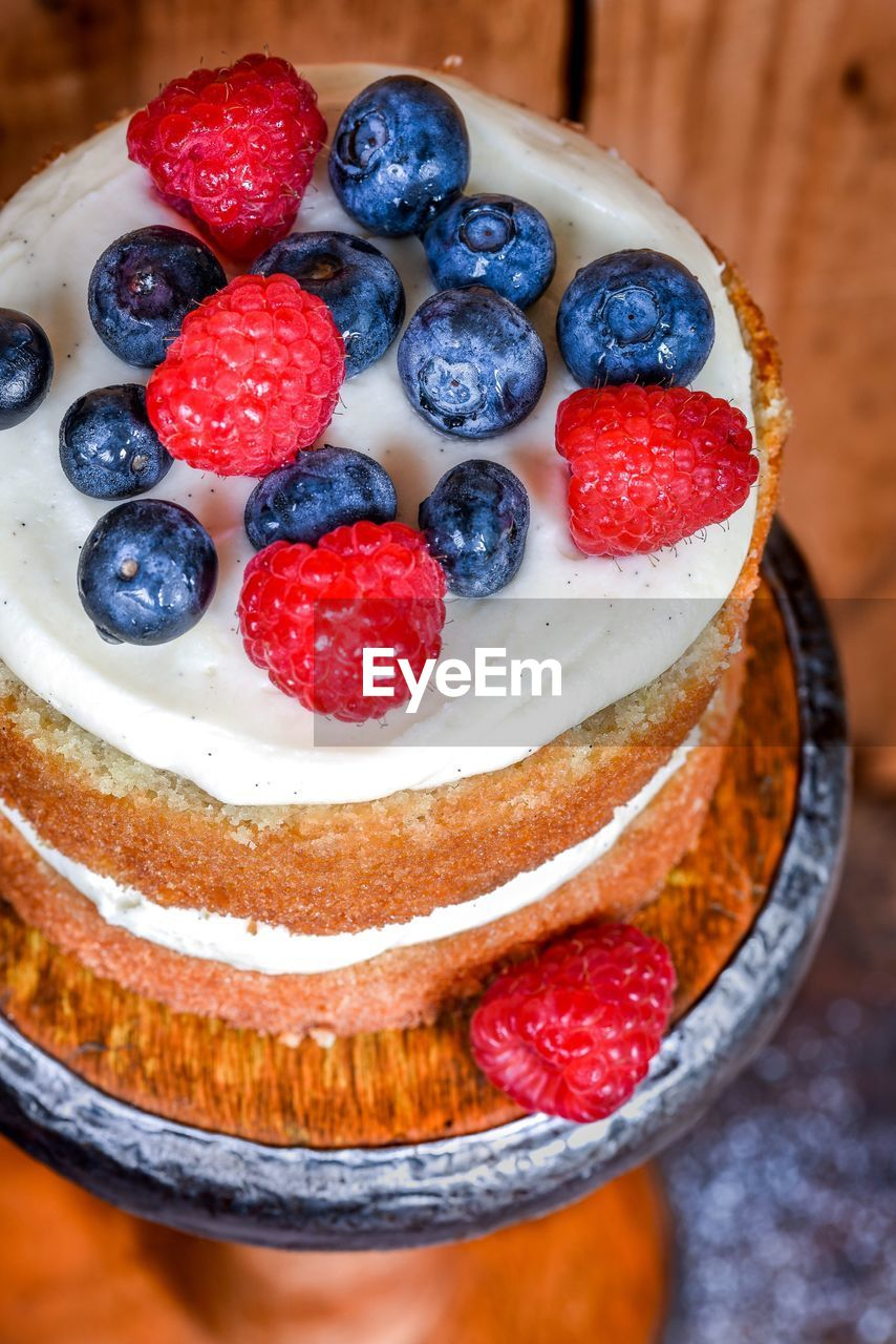 High angle view of cake garnished with blueberries and raspberries on table
