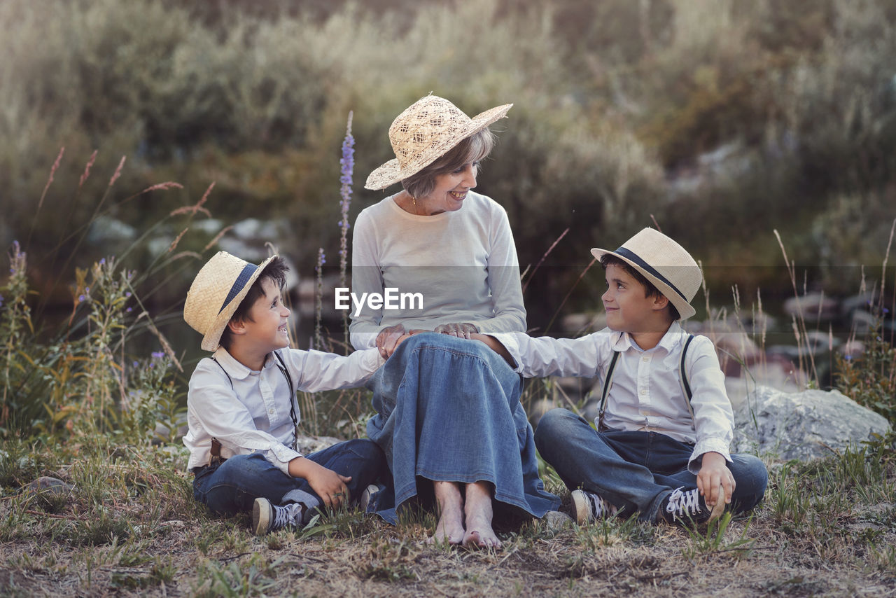 Full Length Of Grandmother With Grandsons Sitting On Field