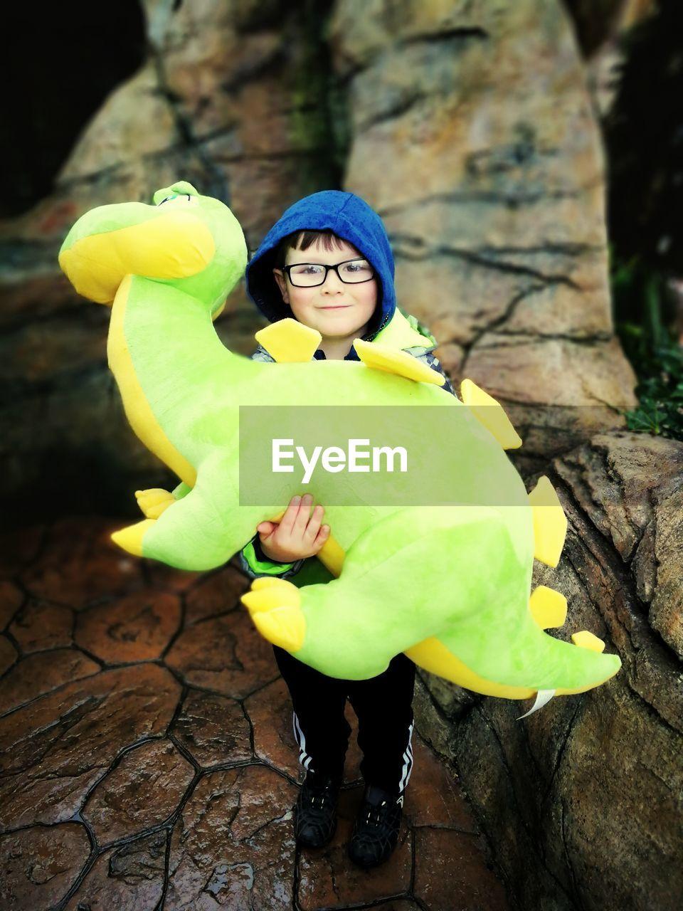Full length portrait of boy holding dinosaur studded toy