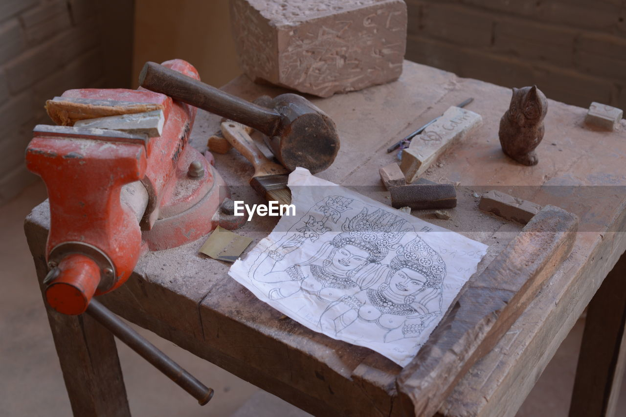 High Angle View Of Drawings And Work Tools On Table At Workshop