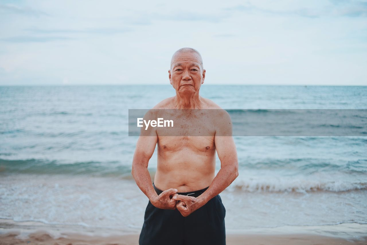 Portrait of shirtless senior man flexing muscles while standing at beach