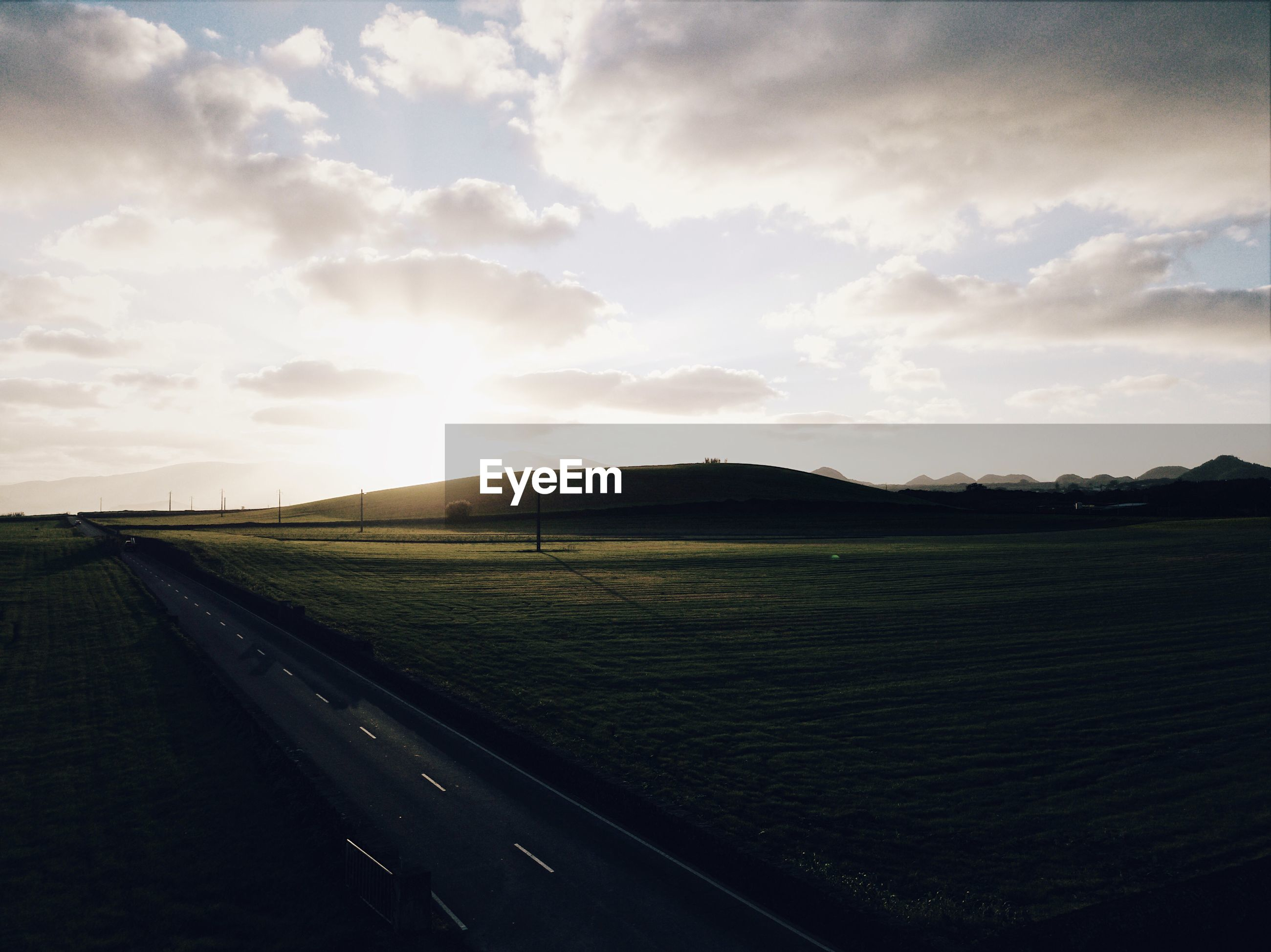 Scenic drone view of field against sky during sunset