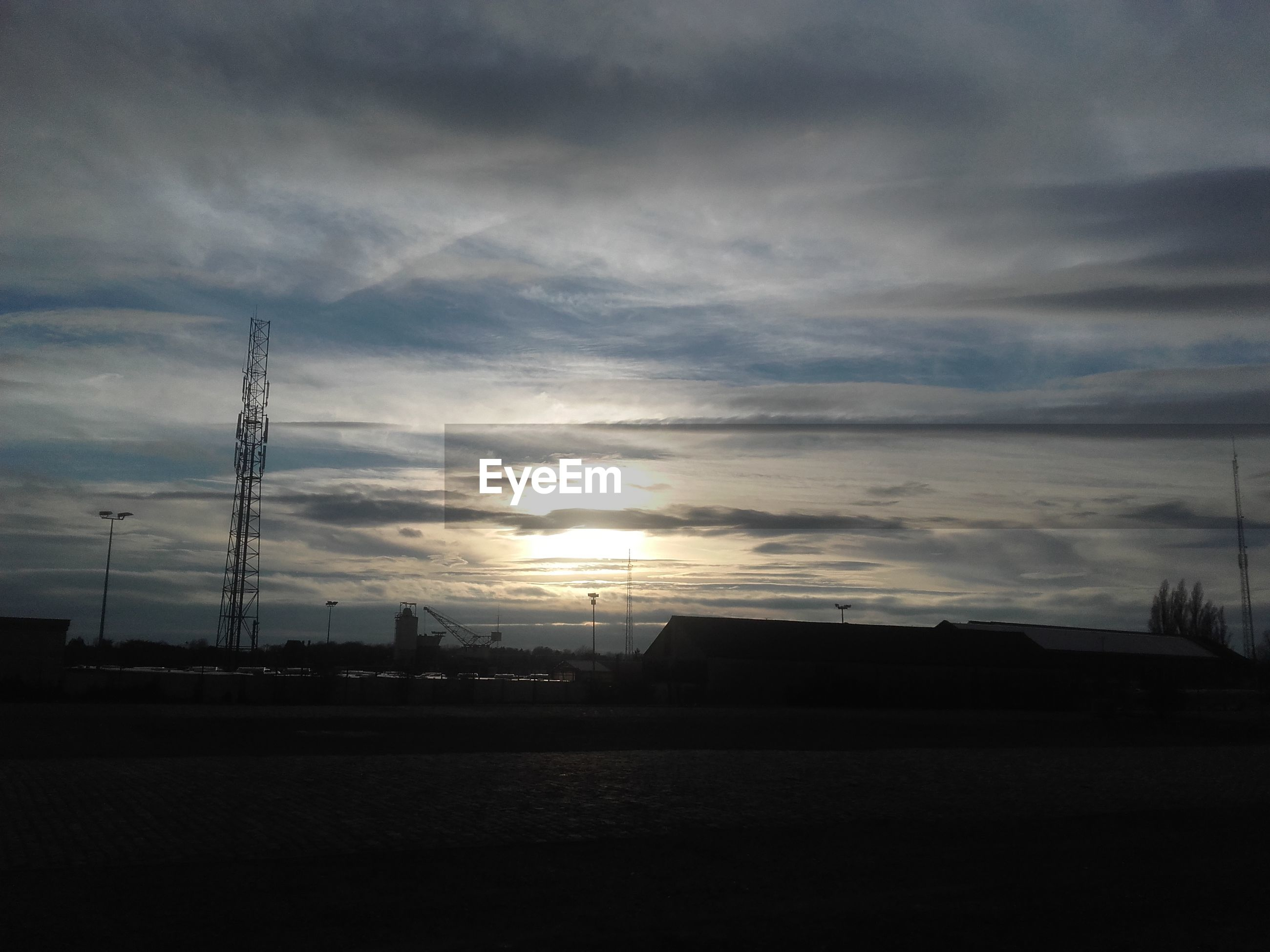 sunset, silhouette, sky, electricity pylon, cloud - sky, built structure, power line, architecture, building exterior, sun, connection, electricity, street light, cloud, orange color, cloudy, nature, sunlight, outdoors, dark