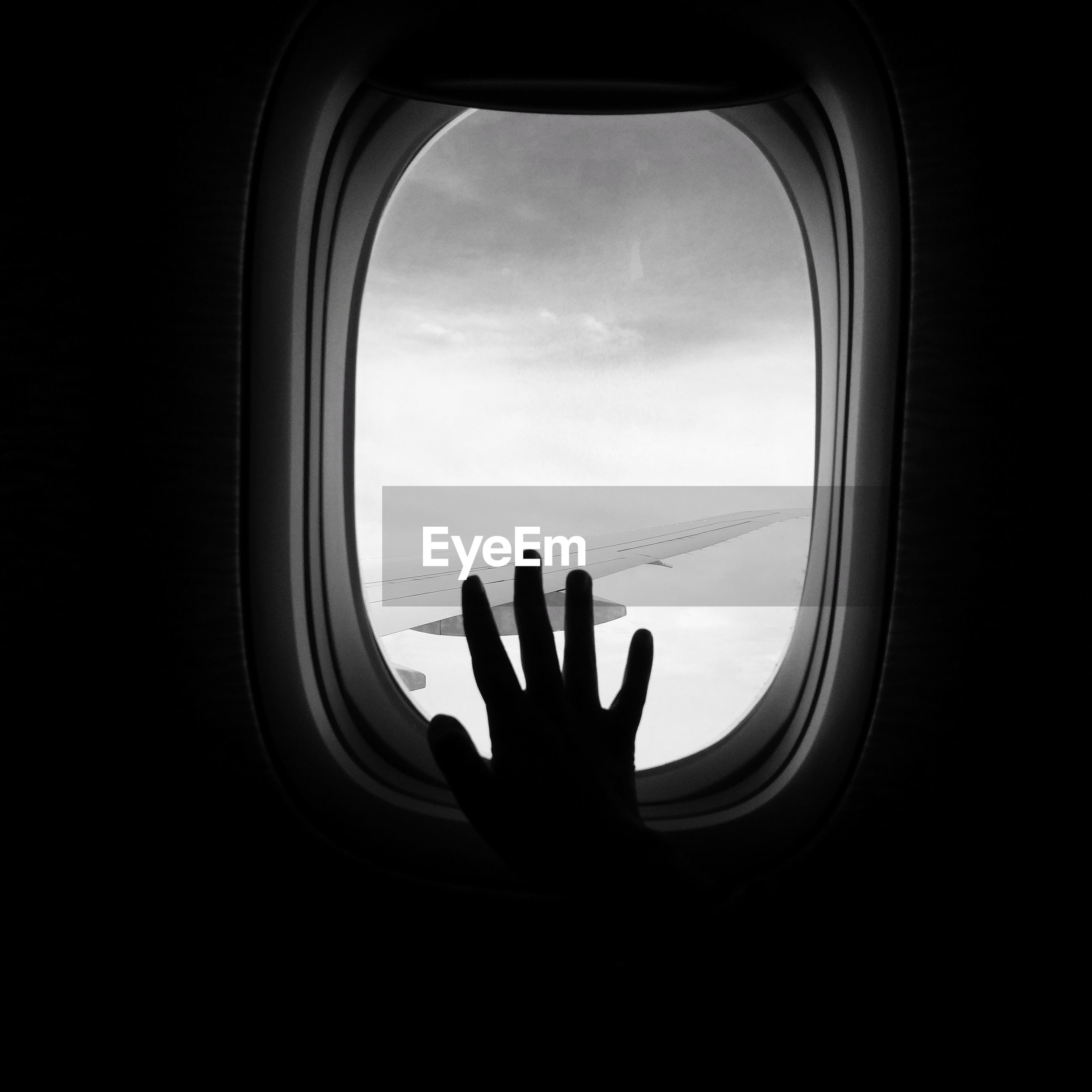 Silhouette hand of person on airplane window