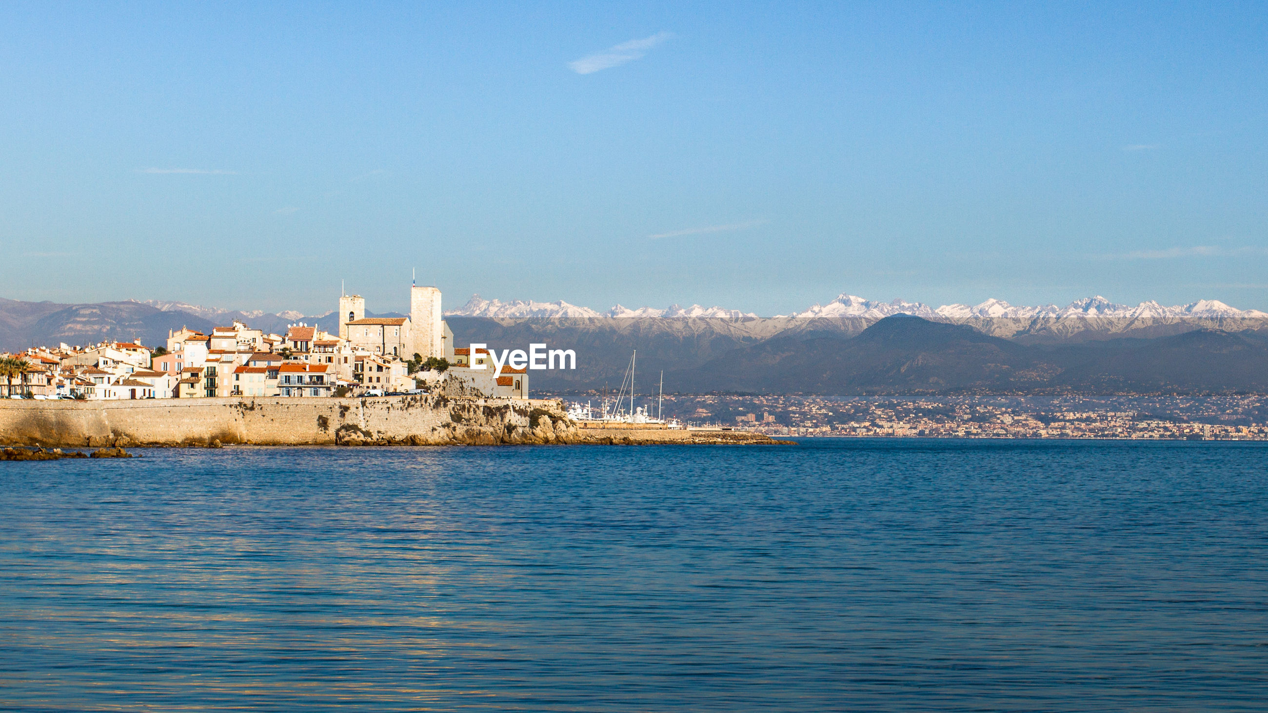 View of sea with snowcapped mountains in background against blue sky