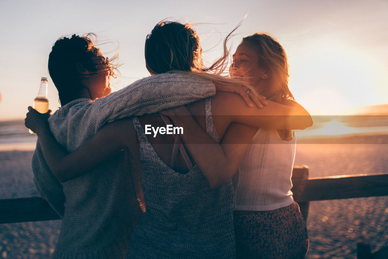 sunset, sky, togetherness, real people, women, two people, leisure activity, bonding, adult, lifestyles, standing, nature, emotion, young women, friendship, casual clothing, waist up, people, young adult, love, positive emotion, outdoors, arm around, lens flare, hairstyle, couple - relationship