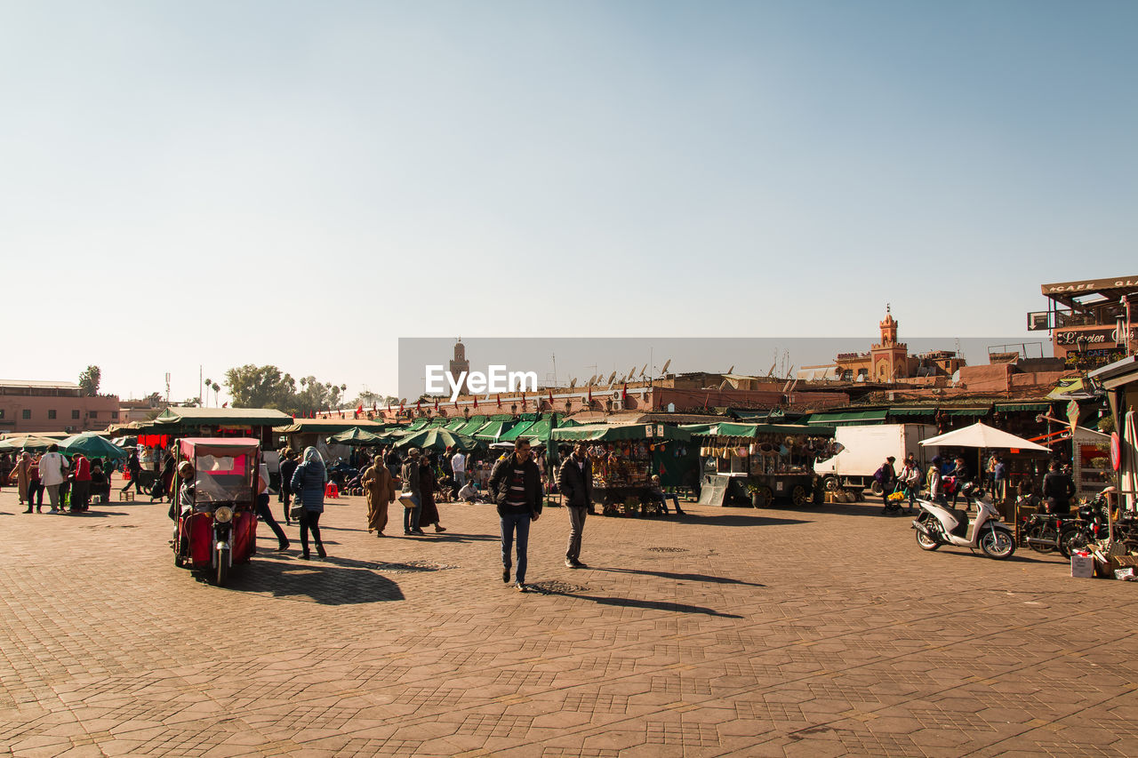 sky, architecture, building exterior, crowd, group of people, large group of people, real people, built structure, city, clear sky, nature, copy space, street, men, transportation, day, women, adult, lifestyles, outdoors, street market