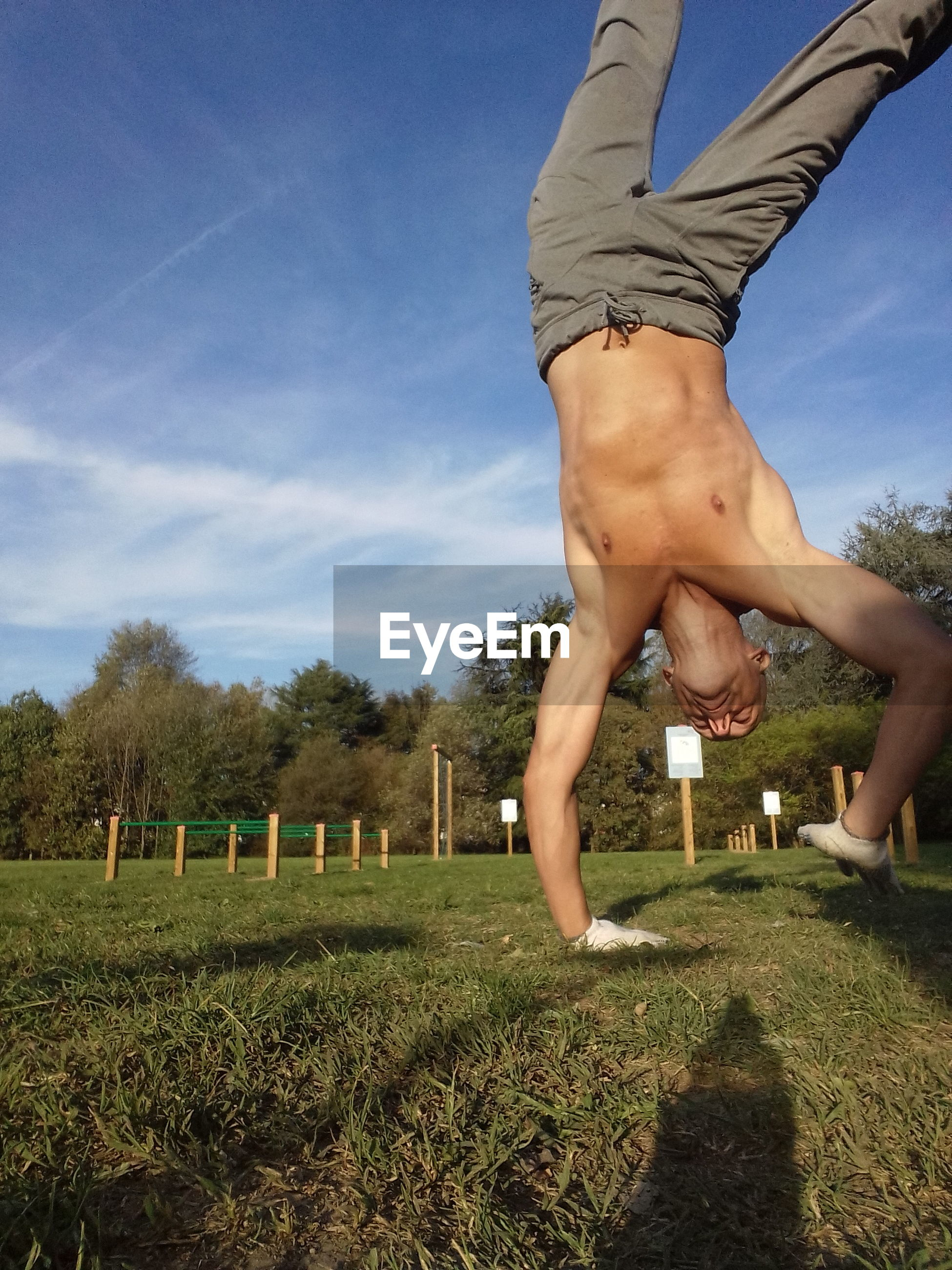 Shirtless man practicing handstand at park against blue sky