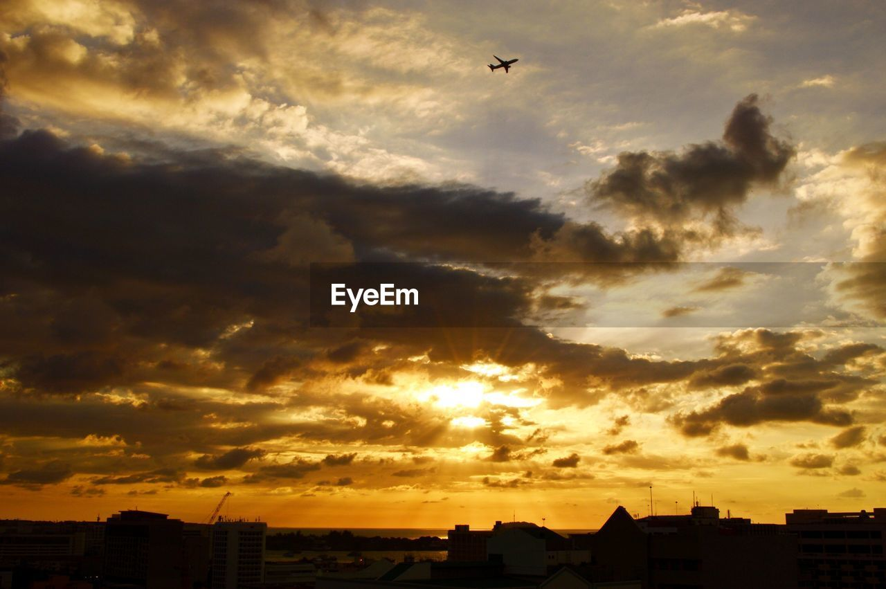sky, cloud - sky, sunset, architecture, building exterior, built structure, orange color, building, nature, city, no people, flying, silhouette, beauty in nature, sunlight, dramatic sky, scenics - nature, outdoors, overcast, low angle view, cityscape, skyscraper