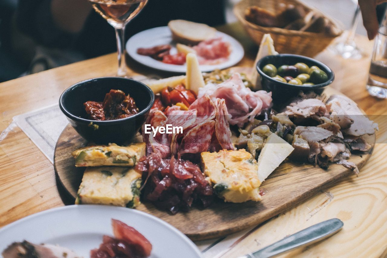 food and drink, food, freshness, table, meat, plate, indoors, ready-to-eat, healthy eating, high angle view, meal, close-up, wellbeing, kitchen utensil, no people, bowl, eating utensil, still life, household equipment, wood - material, glass