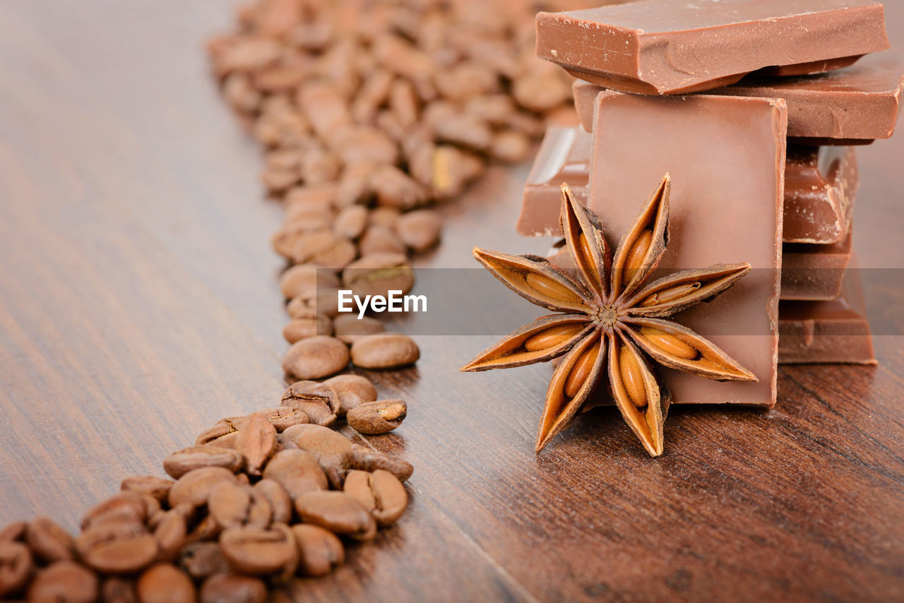 food and drink, food, still life, brown, table, indoors, selective focus, no people, wood - material, freshness, close-up, spice, large group of objects, star anise, high angle view, nut, star shape, cinnamon, raw food, shape