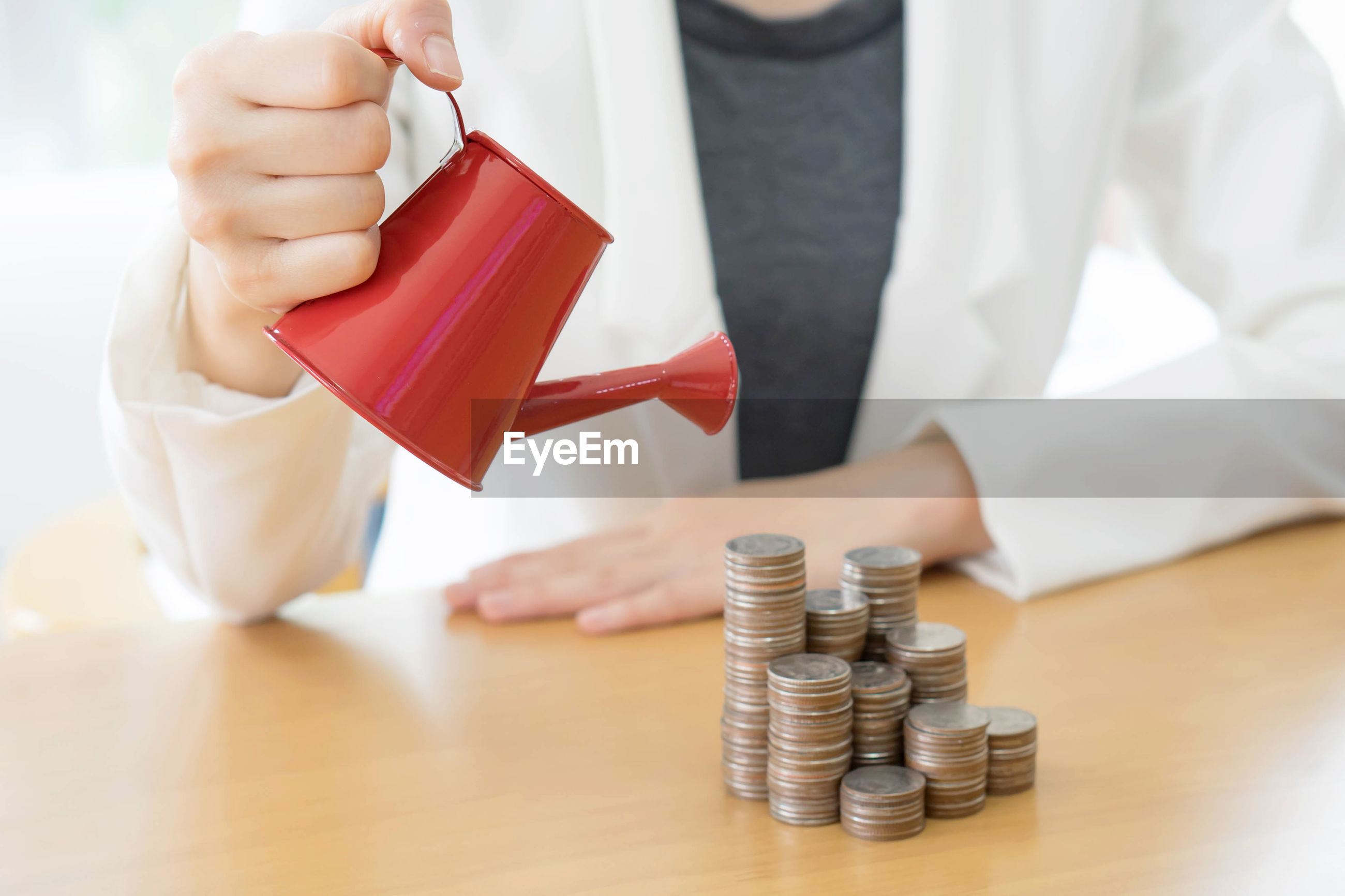 Midsection of businesswoman holding watering can by stacked coins on table